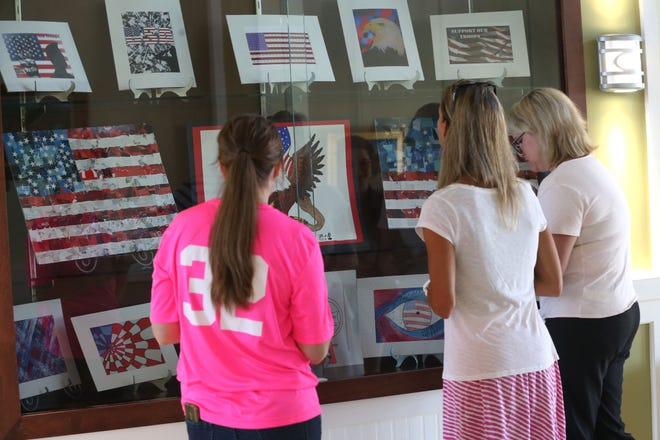 Maclay high school teachers marvel at the Maclay high school art students' work on display at the Tallahassee National Cemetery on October 4, 2018.