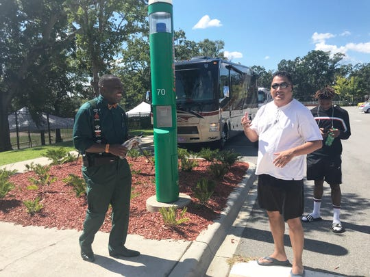 Kelvin Rosier, FAMU senior associate athletics director of facilities and events (left) explains the RV parking situation to fans. The FAMU Village Suites lot is the designated area for all RVs.