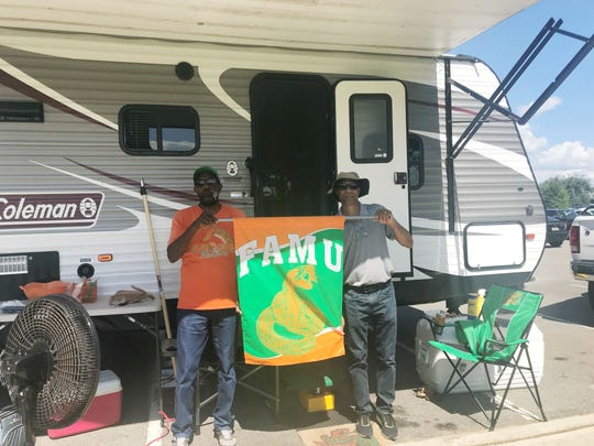 Ivory Turner (left) of Perry and Roderick Allen, Sr. of Tallahassee set up their RV on Wednesday. All RV parking is sealed off at the FAMU Village Suites.