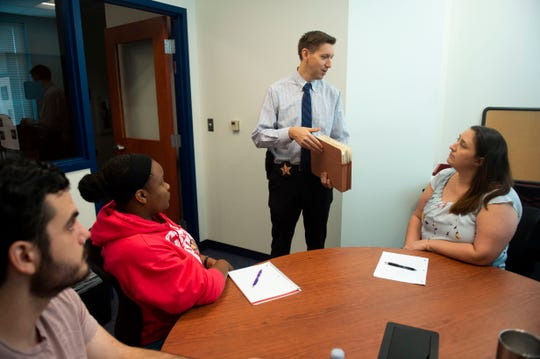 "Dan DuLac (center), detective with the Martin County Sheriff's Office, presents a a box of original reports and records from an old Martin County cold case to a group of Indian River State College criminal justice students (from left) Jeffrey Norris, of Port St. Lucie, Nichole Bradley, of Vero Beach and Kristy Marcellaro, of Port St. Lucie, on Thursday, Oct. 4, 2018, at the Treasure Coast Public Safety Training Complex at IRSC in Fort Pierce. The partnership between IRSC and the Martin County Sheriff's Office is for the college's new applied-learning initiative called the Institute for Cold Case Investigation, led by Kimberlie Massnick (not pictured), an assistant professor. ""I think it's interesting,"" DuLac said of the course. ""It's neat to see people so excited about doing what I do everyday."""