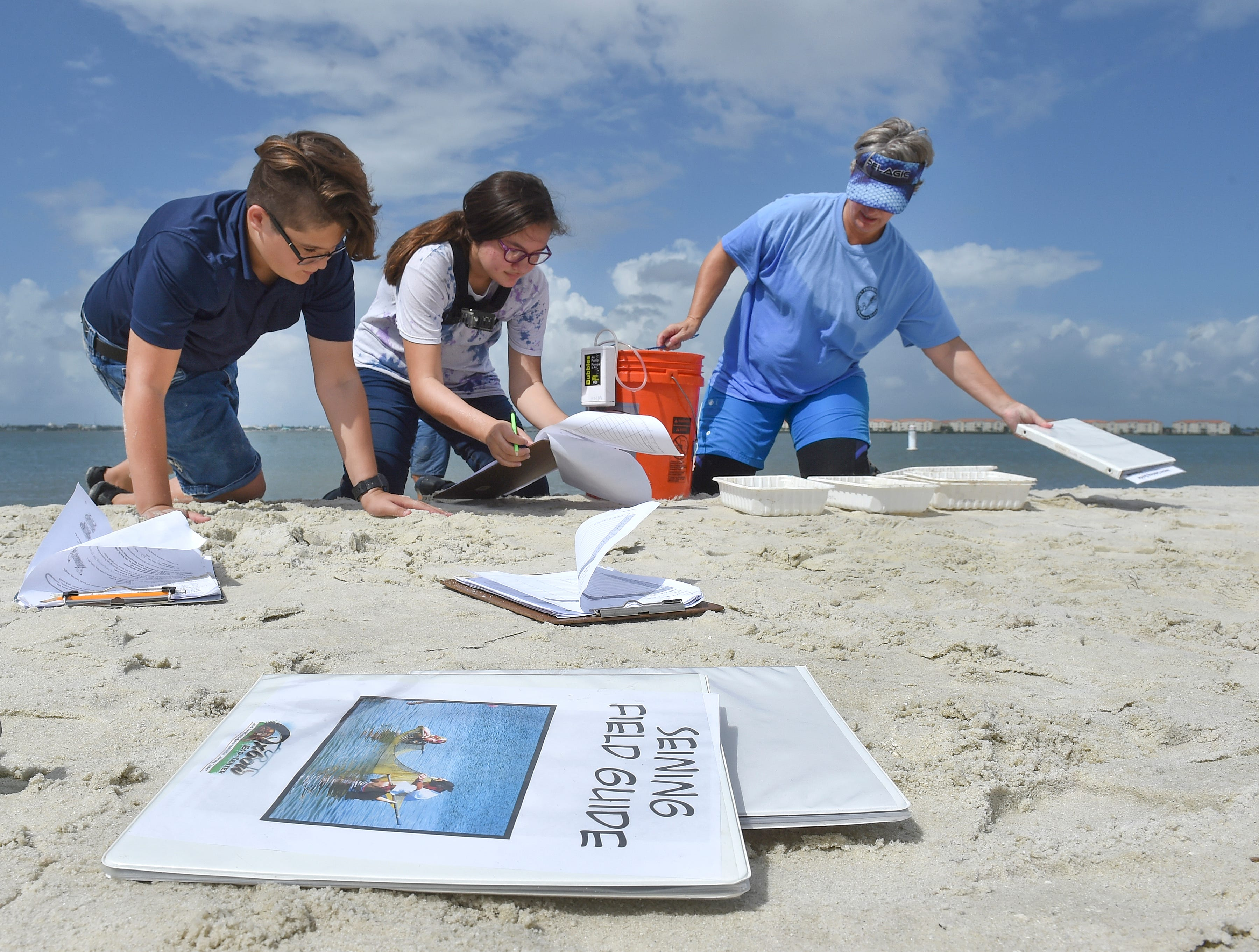"St. Lucie West K-8 students (from left) Christian Ordenana, 12, and Abigail Rivero, 12, help Wren Underwood, senior education coordinator at the Oxbow Eco-Center, of Port St. Lucie, as they record their data from seining in the Indian River Lagoon, capturing mostly comb jellies, transparent marine invertebrates, at Jaycee Park Thursday, Oct. 4, 2018, in Fort Pierce. Sixteen seventh-grade students from St. Lucie West K-8 school, along with their environmental partner, Oxbow Eco-Center, were participating in the ""A Day in the Life of the Indian River Lagoon"", a community-based citizen science and experimental research program to have students, teachers, and environmental experts collaborate in collecting water samples and biological inventories along the Indian River Lagoon. Students and teachers paired with natural resource organizations from Volusia County south through Palm Beach County, testing the health of the entire length of the lagoon. ""Environmental education is such an important component of education and I think every citizen, every person in our community needs to understand how natural systems work and what we can do to help them,"" Underwood said."