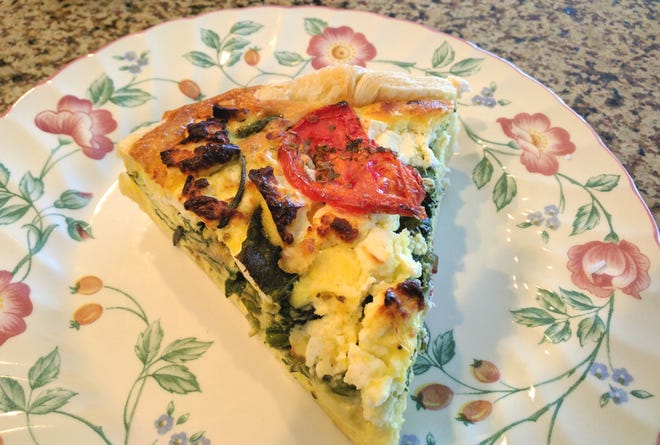 A large slice of AKOHO (A Kitchen of Her Own) spinach, tomato, asparagus, and feta quiche.