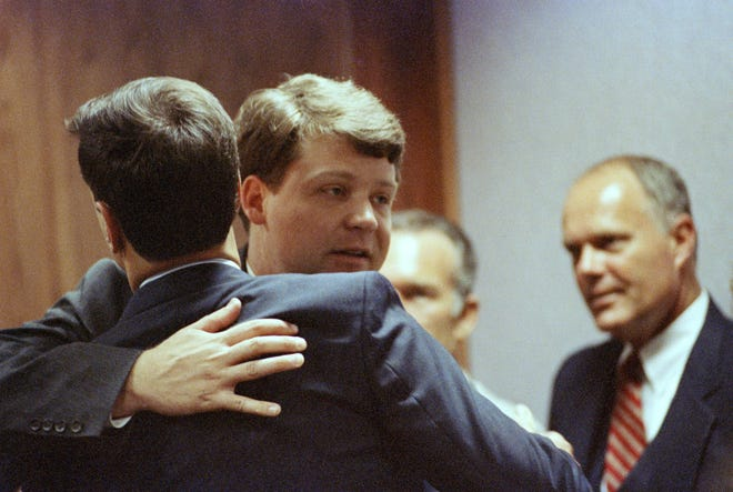 Los Angeles police officer Laurence Powell, center, is hugged by former LAPD officer Timothyn Wind as Sgt. Stacy Koon looks on from the background, right, after the verdict in the Rodney King beating trial was read in Simi valley on April 29, 1992.