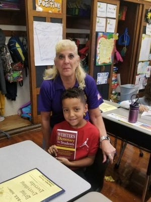 Each year members of the Millville Elks Lodge No. 580 donate dictionaries to every third-grader in the Millville and Maurice River Township school districts. Arlene Hickman, Exalted Ruler, Millville Elks Lodge No. 580, presents a dictionary to Gerald Ortiz, a third grader at Bacon School in Millville.
