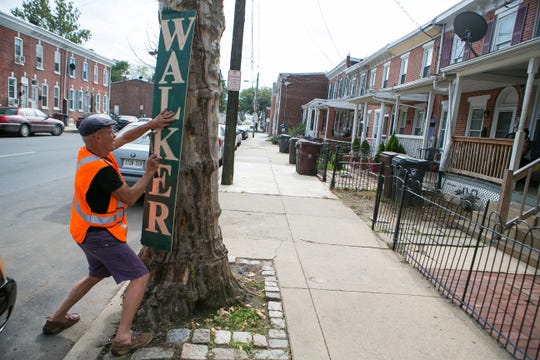 Republican congressional candidate Scott Walker puts up a campaign sign in Wilmington.