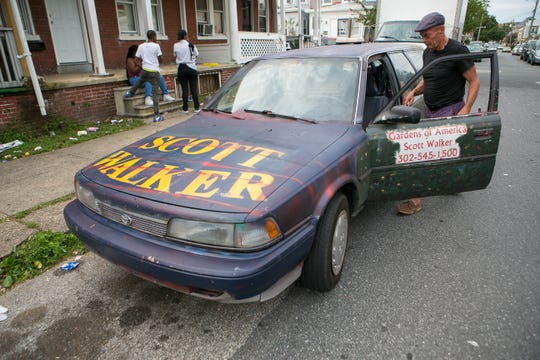 Republican Congressional candidate Scott Walker rolls through Wilmington putting up campaign signs.
