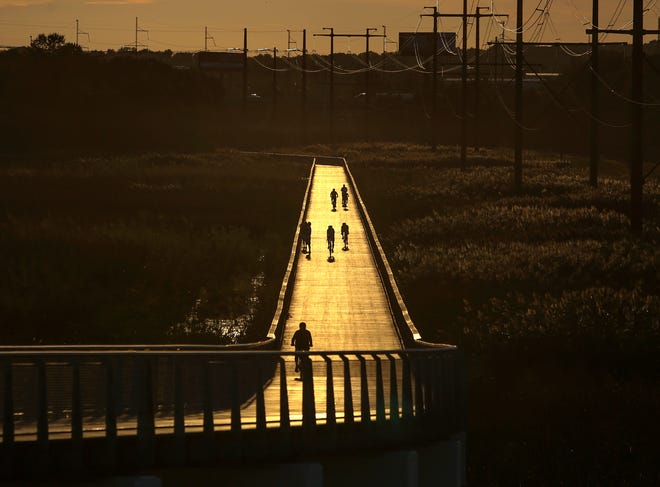Bicyclists and walkers use the Jack A. Markell Trail where it carries over marshes south of Wilmington.
