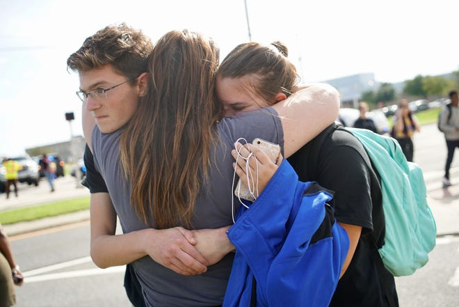 A parent is reunited with her kids after Middletown High School's lockdown is lifted on Thursday.