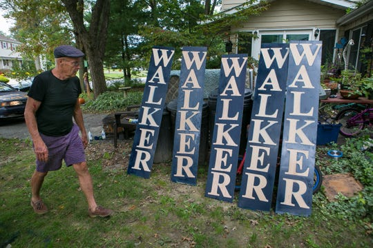 Republican U.S. House candidate Scott Walker walks past a row of his campaign signs he recently painted to ensure they are ready to be used.