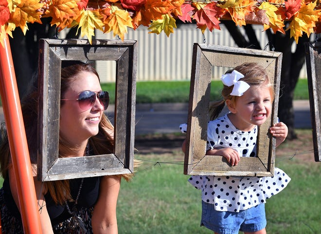 Jana Schmader and her daughter, Jentry, 2, pose for a picture in frames at the Pumpkin Patch behind University United Methodist Church Thursday.