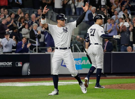 New York Yankees' Aaron Judge, left, reacts after scoring on a double by Aaron Hicks during the sixth inning of the American League wild-card playoff baseball game, Wednesday, Oct. 3, 2018, in New York. (AP Photo/Frank Franklin II)