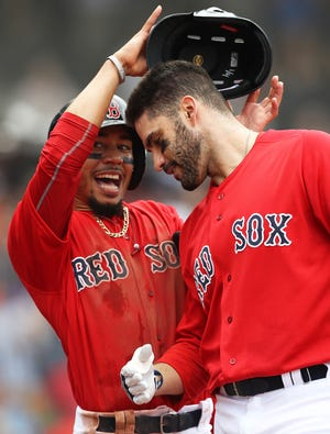 Mookie Betts helps Boston teammate J.D. Martinez celebrate one of his 43 home runs this season.