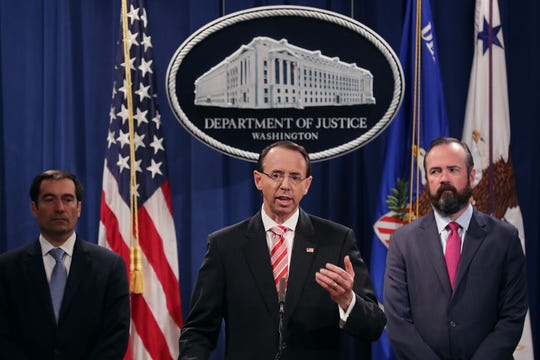 Assistant Attorney General John Demers (L) announces charges July 13, 2018, against 12 Russian intelligence agents for hacking computers used by the Democratic National Committee, with Deputy Attorney General Rod Rosenstein (C) and Acting Principal Deputy Attorney General Edward O'Callaghan (R).