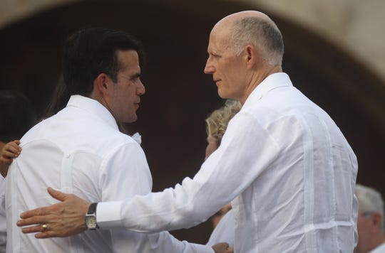 Puerto Rico Gov. Ricardo Rossello, left, greets Florida Gov. Rick Scott, right, during an event to remember victims of Hurricane Maria at the Castillo San Cristobal in Old San Juan, Puerto Rico, Sept. 20, 2018.