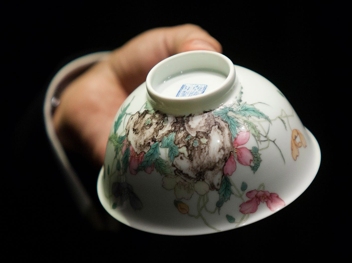 A staff member from Sotheby's auction house displays the Falangcai Poppy Bowl, which according to Sotheby's is one of the greatest examples of Qianlong Falangcai porcelain in private hands, in Hong Kong, China.