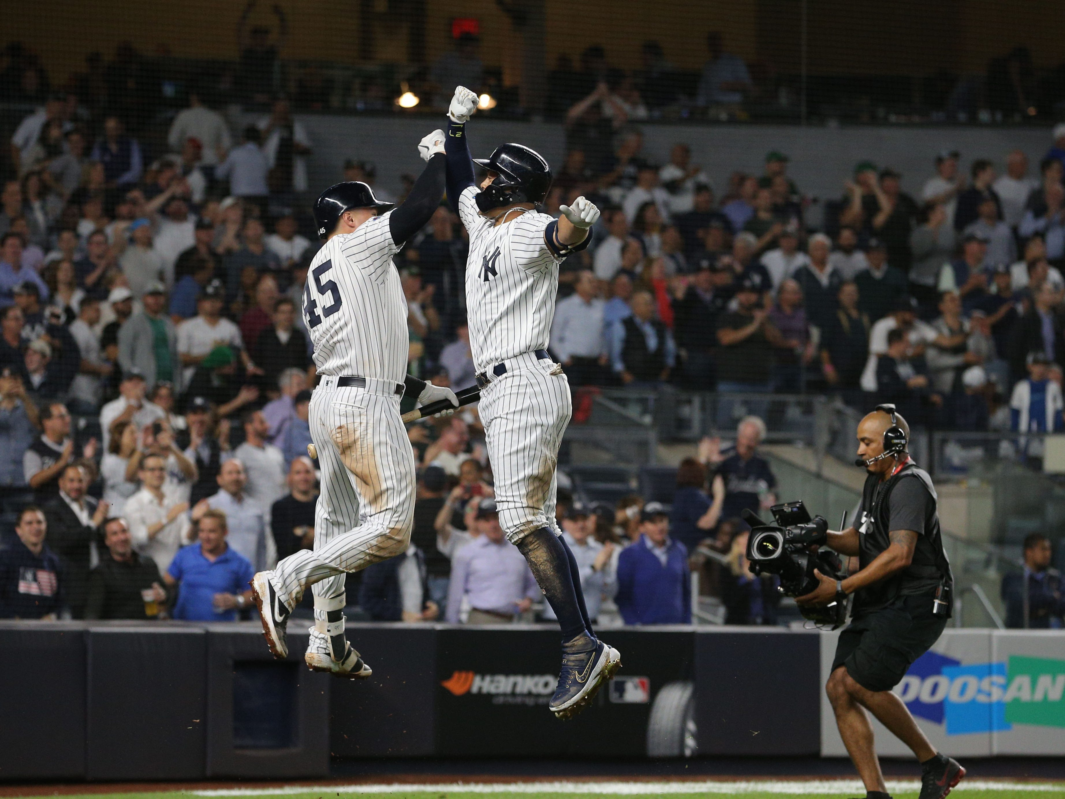 AL wild card: Yankees' Giancarlo Stanton and Luke Voit celebrate Stanton's solo home run in the eighth inning.
