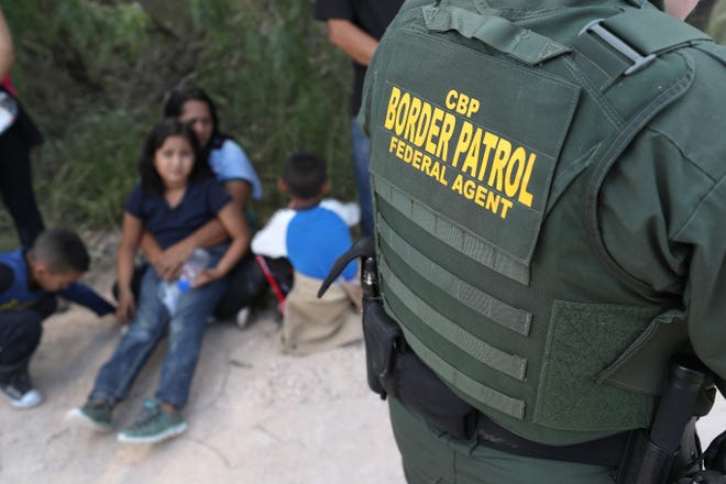 Central American asylum seekers wait as U.S. Border Patrol agents take them into custody on June 12, 2018, near McAllen, Texas. The families were then sent to a U.S. Customs and Border Protection processing center for possible separation.