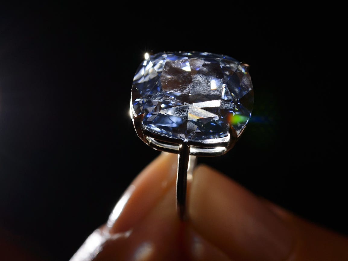 A model holds a 12.03-carat blue diamond during a press preview by auction house Sotheby's in Geneva. The 12.03-carat blue diamond sold for $48,468,158 USD, a world record for a gemstone at auction, on Nov. 11 2015, in Geneva. Categorized as a fancy vivid blue diamond, the Blue Moon, discovered in South Africa in Jan. 2014, is the largest cushion-shaped stone in that category to ever appear at auction.