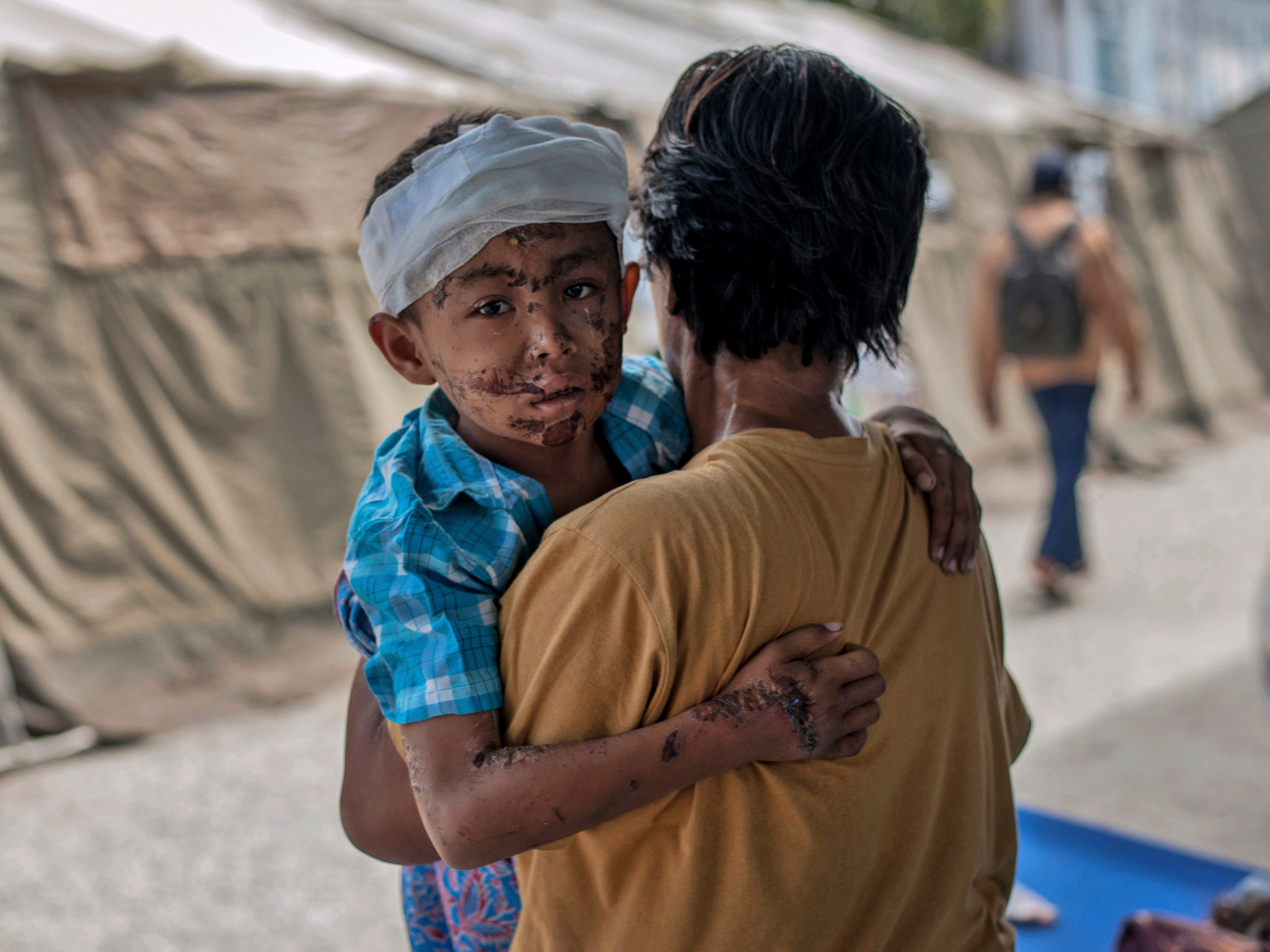 A boy injured during the tsunami is carried by his relative at a makeshift hospital in Palu, Central Sulawesi, Indonesia, Oct. 4, 2018.