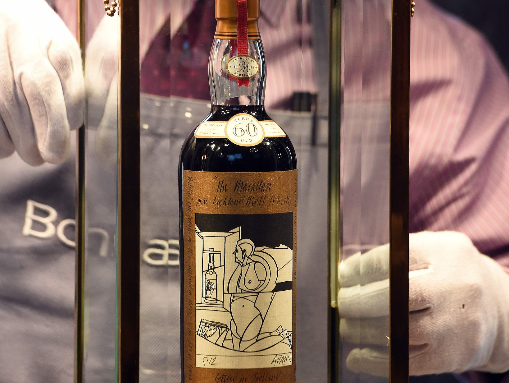 A Bonhams porter shows the bottle of Macallan Valerio Adamai 1926 whisky which sold for a world record sale price of £700,000 at auction in Edinburgh on Oct. 3, 2018. - The whisky, which was in a vat for 60 years from 1926 then bottled, fetched £700,000 plus a £148,000 sales premium to make it the most expensive whisky for £848,000 or $1,104,403.82 USD.