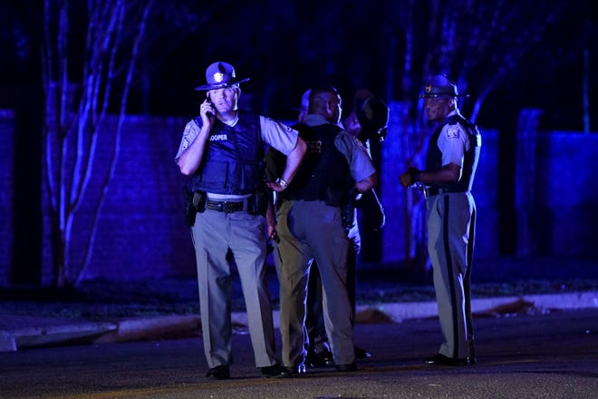 South Carolina state troopers gather on Hoffmeyer Road near the Vintage Place neighborhood where several law enforcement officers were shot, one fatally, Wednesday, Oct. 3, 2018, in Florence, S.C.