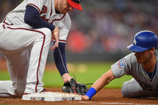 Braves first baseman Freddie Freeman puts down a tag on the Dodgers' Cody Bellinger during a game in July.