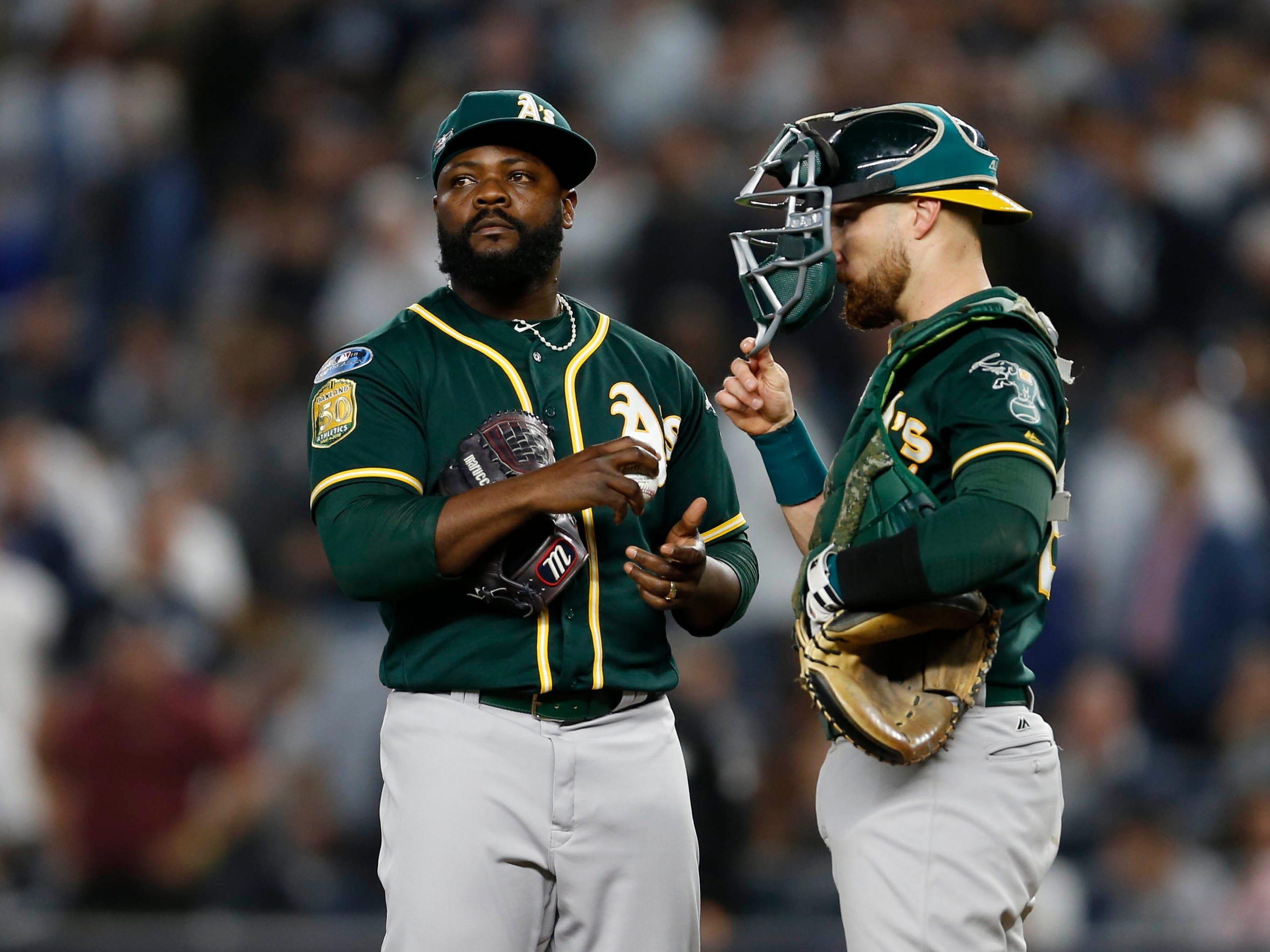 Oct 3, 2018; Bronx, NY, USA; Oakland Athletics Fernando Rodney (56) and catcher Jonathan Lucroy (21) meet at the mound during the sixth inning against the New York Yankees  in the 2018 American League wild card playoff baseball game at Yankee Stadium. Mandatory Credit: Adam Hunger-USA TODAY Sports
