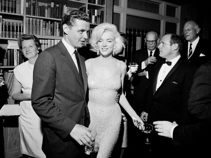 "In this May 19, 1962 photo provided by the John F. Kennedy Presidential Library and Museum, actress Marilyn Monroe wears the iconic gown that she wore while singing ""Happy Birthday"" to President John F. Kennedy at Madison Square Garden, during a reception in New York City. Standing next to Monroe is Steve Smith, President Kennedy's brother-in-law."