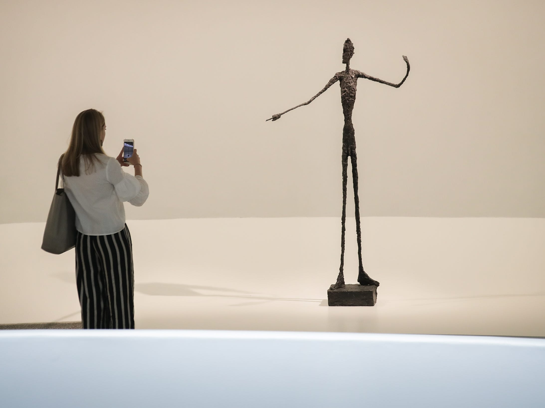 A woman stops and photographs 'Man Pointing,' a 1947 bronze sculpture, at a retrospective exhibition of work by Swiss sculptor and artist Alberto Giacometti at the Guggenheim Museum, June 7, 2018 in New York. With fees, Christie's auction house sold the sculpture for $141.3 million USD, on May 11, 2015.