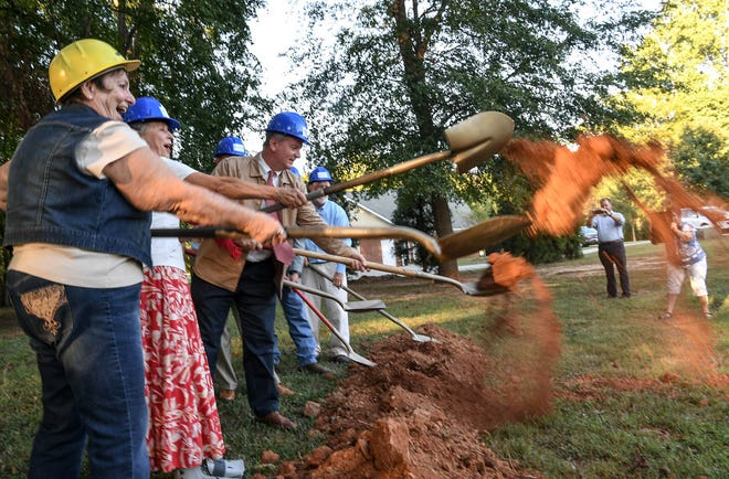 Gloria Bolte, left, of Anderson joins in turning over dirt during a groundbreaking event for new homes at the Calvary Home for Children site in Anderson on Thursday.