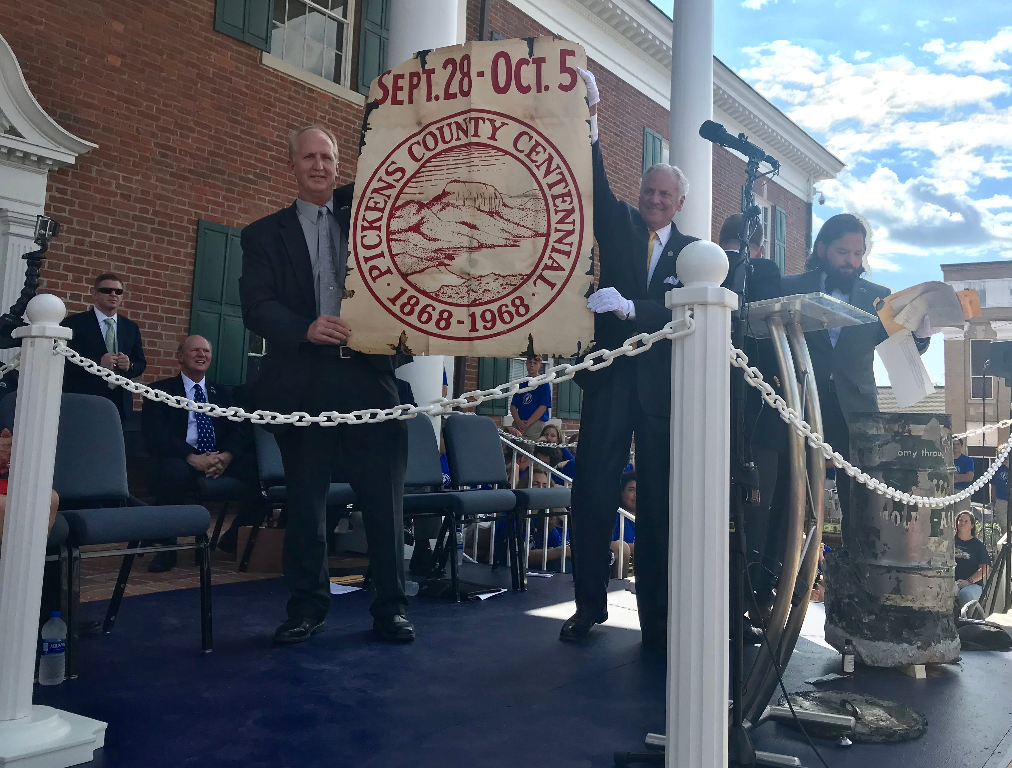 Pickens County Councilman Wes Hendricks, left, holds a banner from the county's Centennial in 1968 with Gov. Henry McMaster.