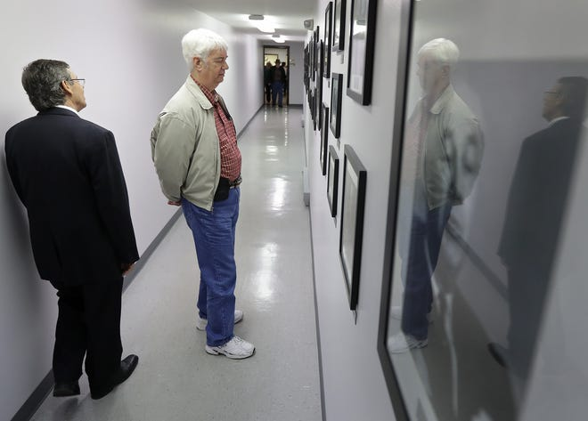 Regional field director Wayne Morrow, left, and Ivan Price, a visitor from North Carolina, look at photos in the Robert Welch Hall during Friday's open house at the John Birch Society headquarters in Grand Chute. Wm. Glasheen/USA TODAY NETWORK-Wisconsin