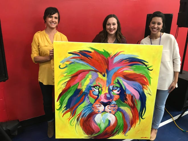 Karen Wiersig, left, poses with Abilene Christian University student Martha Coates and Lee Elementary's Courtney Oglesby Friday. Coates, who created a colorful lion head painting for the Lee Lions to display at their school, was greeted by roaring applause when the creation was unveiled.