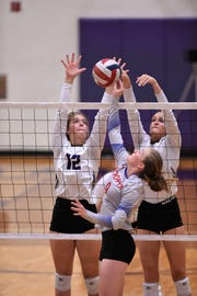 Wylie's Madison Burden (12) and Karis Christian (4) go up for a block against Cooper at Bulldog Gym on Friday, Oct. 5, 2018.