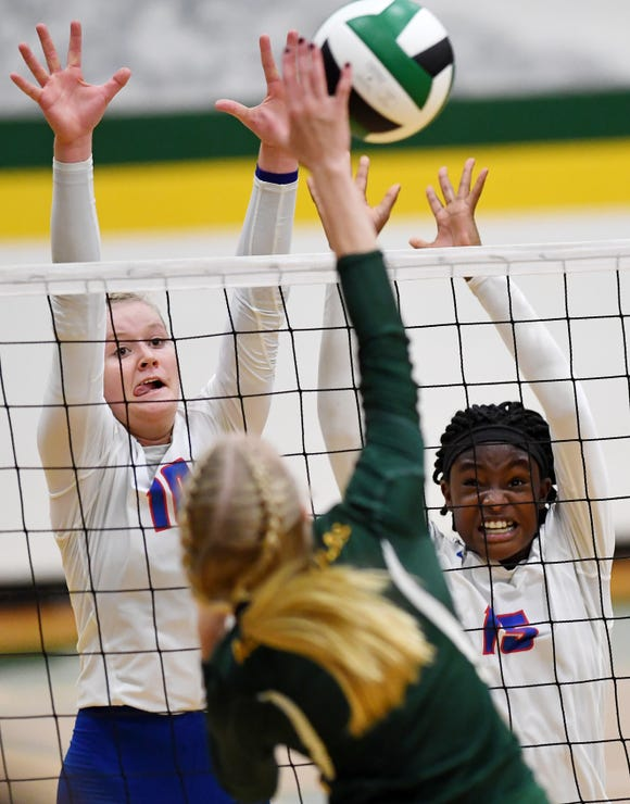 West Henderson's Malia Moore, left, and Daija Jackson attempt to block a spike from Reynolds' Abby Hutzler in a conference match Oct. 4, 2018 in Asheville.