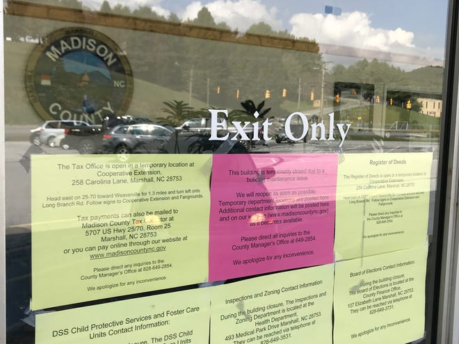 Signs posted at Madison County's administrative office building tell visitors where department staff has been temporarily relocated. Trace amounts of asbestos were found in floor tiles removed during work inside the 1972 building.