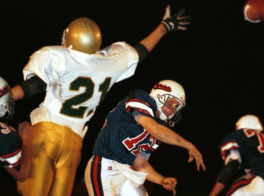 In 1999, Vestal's Chris Slater, left, puts pressure on Binghamton quarterback Luke Stanton, middle, during the first half of play at the East Middle School football field.