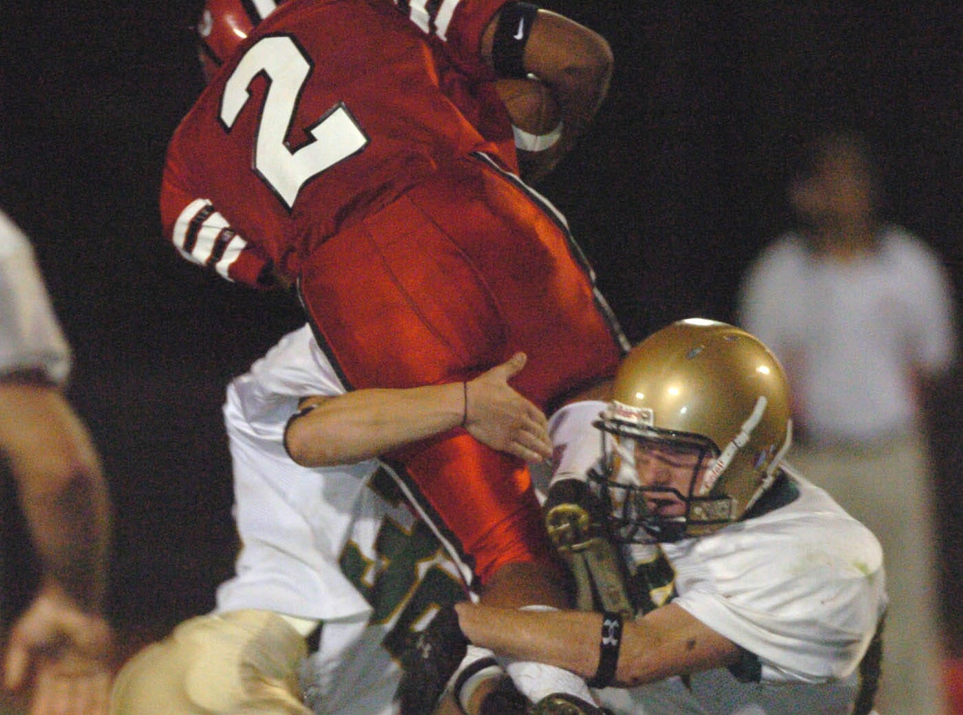 In 2005, Vestal defenders Kevin Godoy, left, and Kenny Sherwod team up to bring down Baldwinsville running back Chris Silva during Class AA football action.
