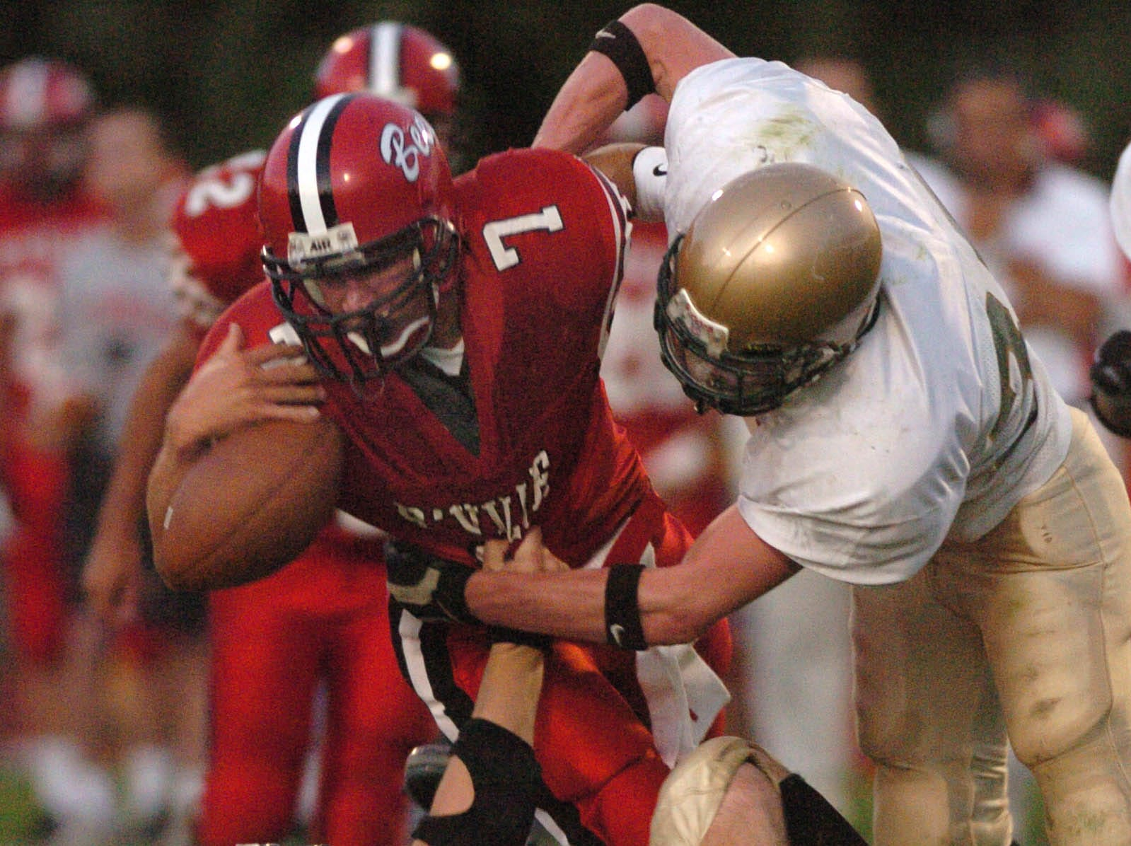 In 2003, Vestal's Trevor Bertrand, left, and Brad Cook force Baldwinsville quarterback Jeremy Boltus to lose the football during Class AA football action on the opening of the 2005 season at Baldwinsville.