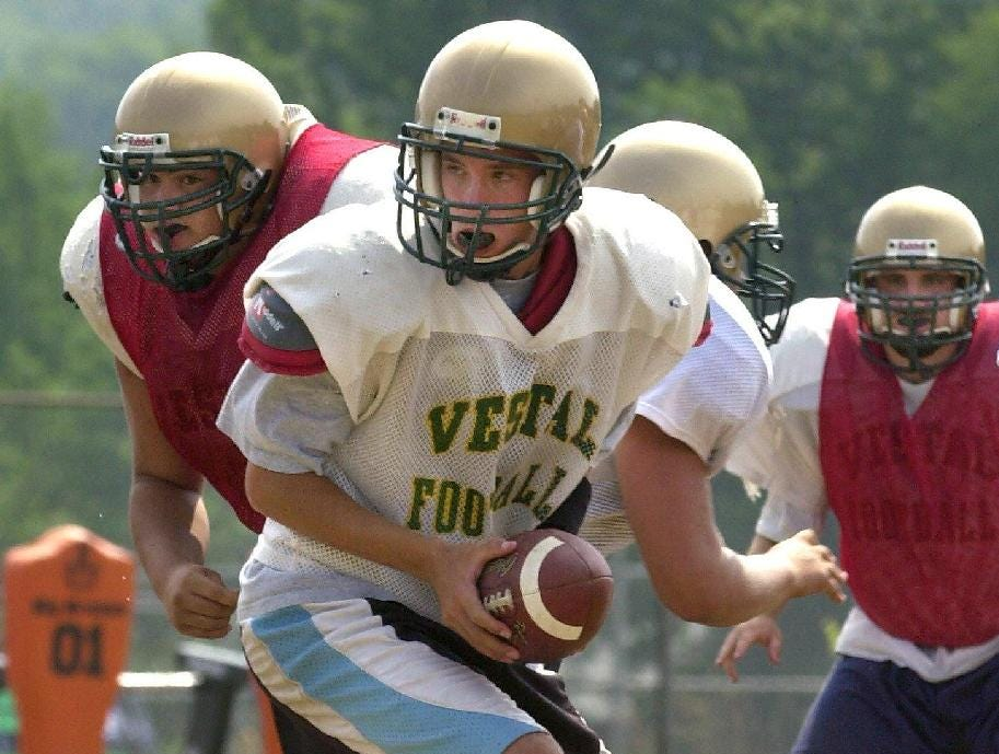 -  -Vestal's quarterback Joe Talbut looks for the handoff while running plays during practice.
