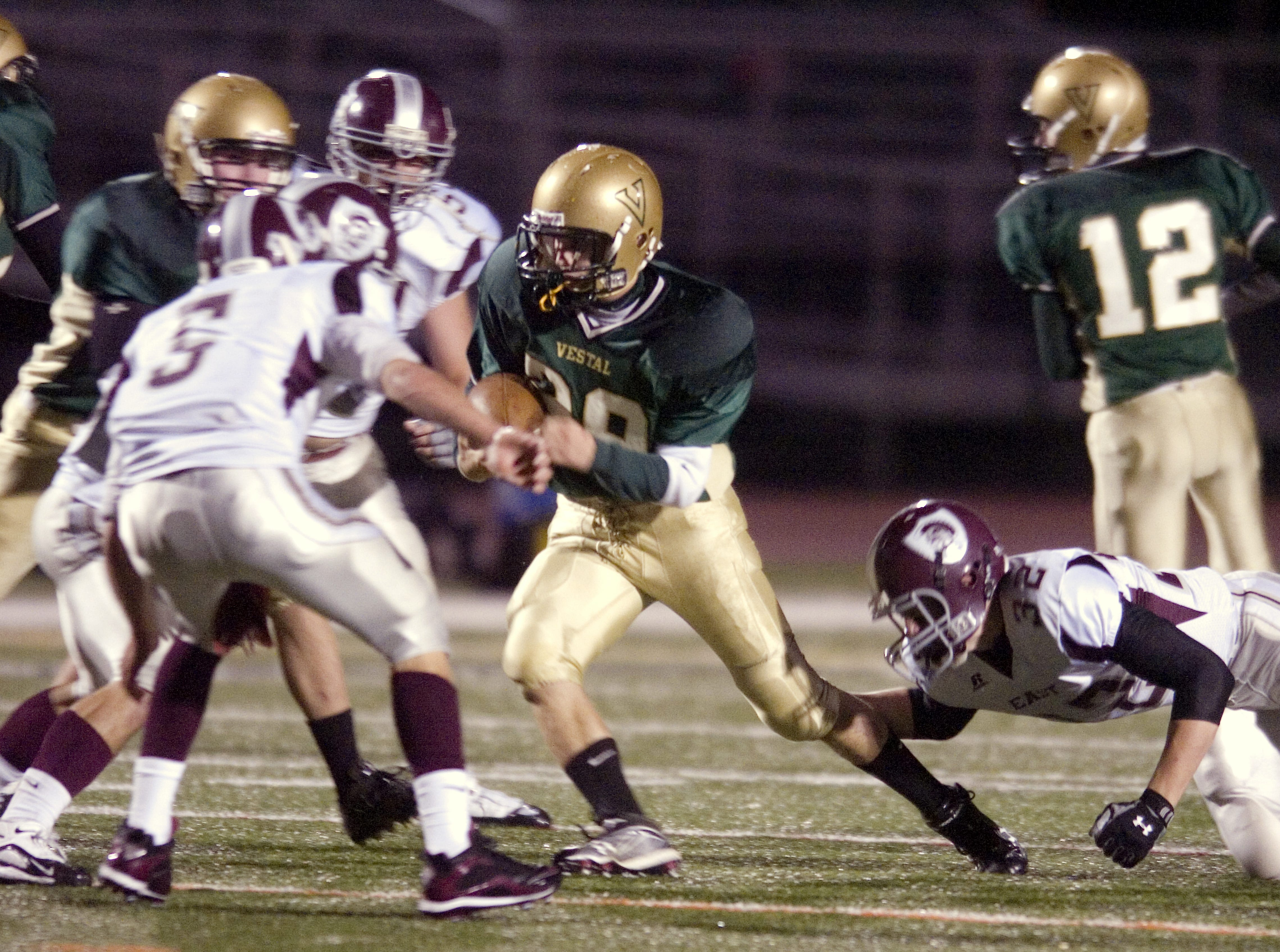 In 2009, Vestal's Brock Leonard, middle, evades Corning East's John Hartman, right, but is met by Brandon Griffin in the first quarter at Dick Hoover Stadium.