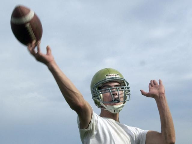 In 2000, Vestal High School quarterback Josh Williams lets a pass fly during opening day of drills.