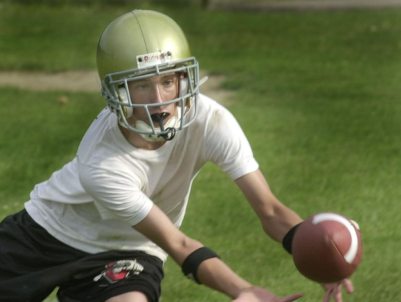 In 2000, Vestal High School receiver and defensive back Conor Talbut watches the football reach his hands during opening day drills.