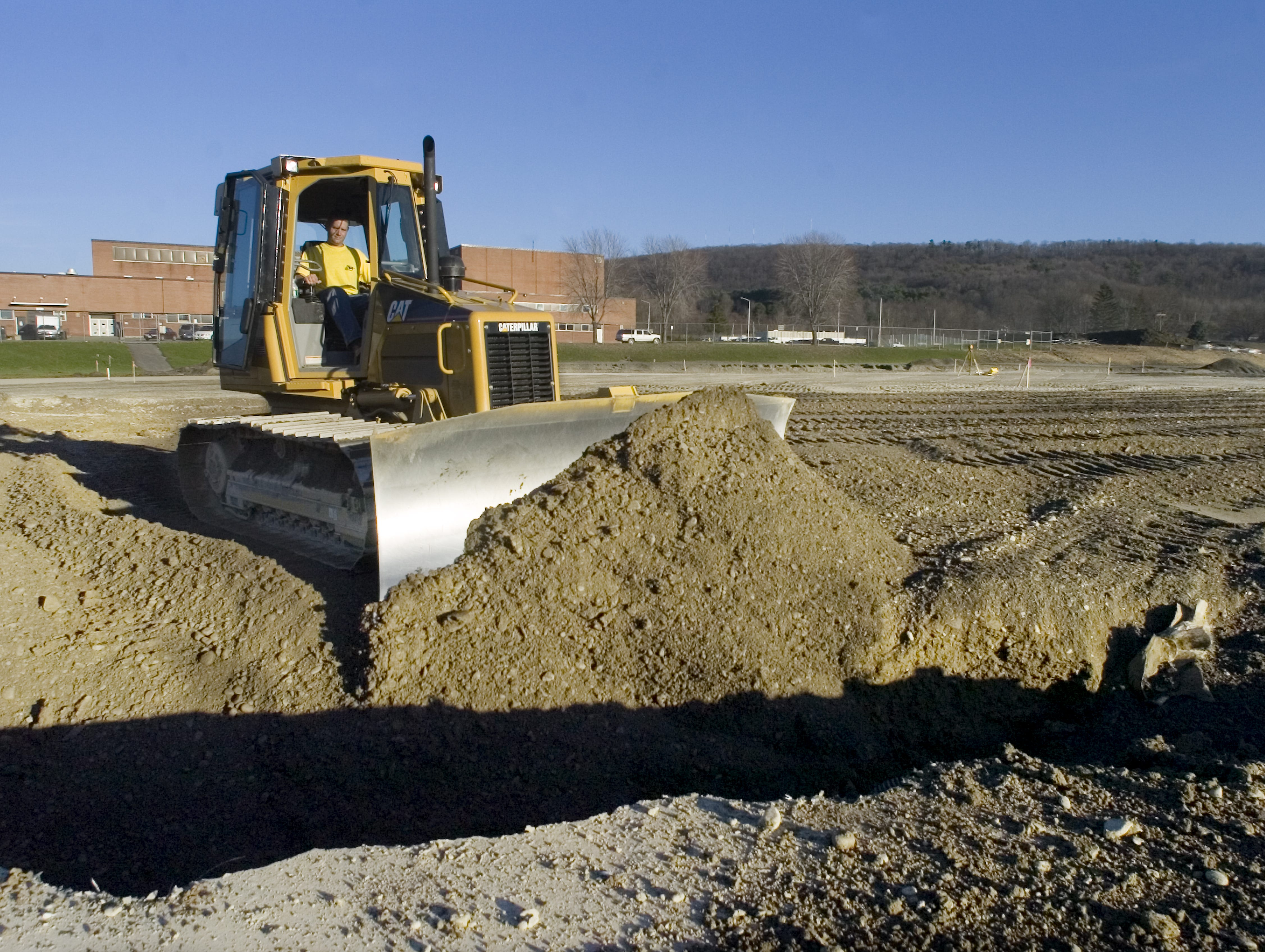 In 2006, Jamin Boland with Boland's Excavating & Topsoil, fills a hole with a bulldozer after old drainage pipe was removed from the old football field in Vestal.