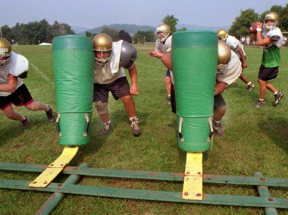 Vestal High School football players practice using a seven man charger (sled). Pictured are (l-r):Brandon Webster, Donnie Younker, Tyson Figuroa, Shannon Smacher. In rear:Craig De Curtis, Kurt Johnson and Mike Young (QB). 1996