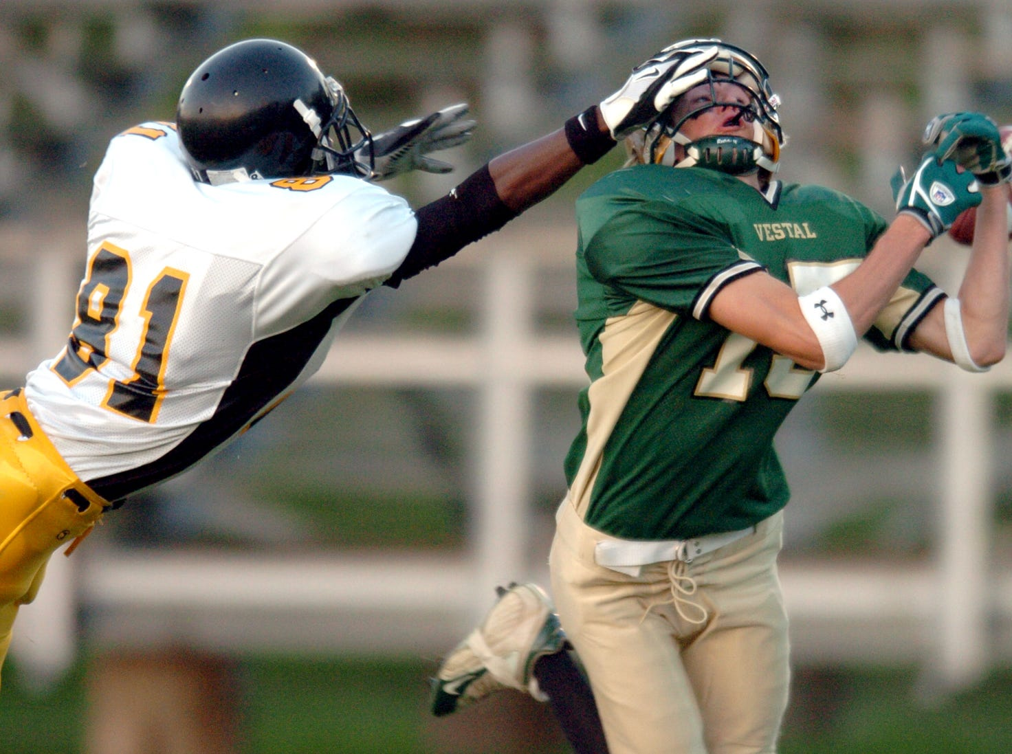 In 2005, Vestal's Matt Gordon, right, fails to catch the football as his face mask is pulled by Henninger's Calvin Williams.