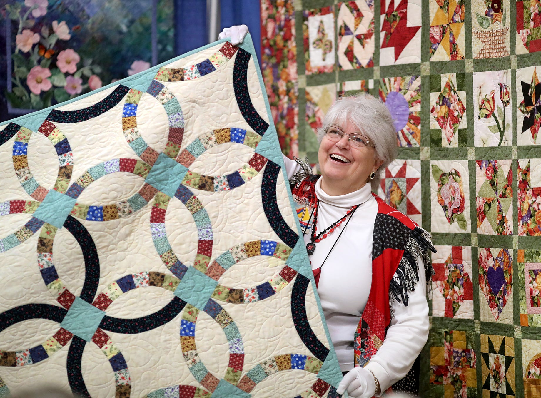 Pat Rosenthal of Gig Harbor laughs at the commentary as she is one of the quilt turners during a quilt demonstration at the West Sound Quilters, show  at Presidents Hall at the Kitsap County Fairgrounds on Friday The show is open from 9am-5pm October 5 & 6, 2018. The annual show features small and large quilts hanging in the hall.