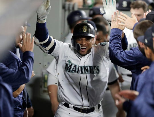 Robinson Cano celebrates with teammates after his home run on Sept. 11 against the Padres in Seattle.