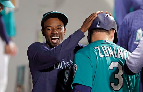 Mariners infielder Dee Gordon congratulates Mike Zunino after Zunino scored during a game against the Rangers on Sept. 28.