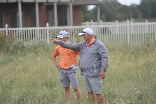 Galion coach Bryce Lehman doles out advice to Spencer Keller in the rough near the 18th green at Red Hawk Run.
